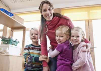 Group picture of female educator and three kids in kindergarten