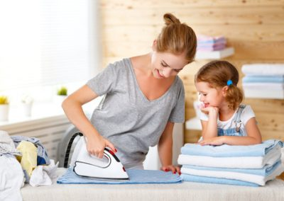 Happy family mother housewife and child daughter ironing clothes