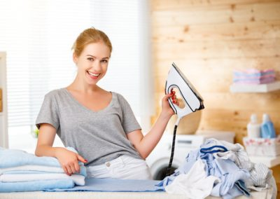 Happy woman housewife ironing clothes   in laundry at home.