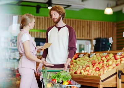 Young couple having argument in supermarket while discussing wha