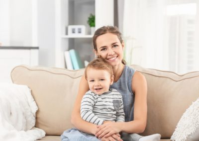 Mother with baby boy on sofa at home