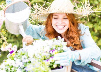 rothaarige Frau im Garten bei den Blumen