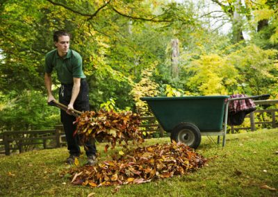 A gardener using a leaf blower to clear up autumn leaves in a ga
