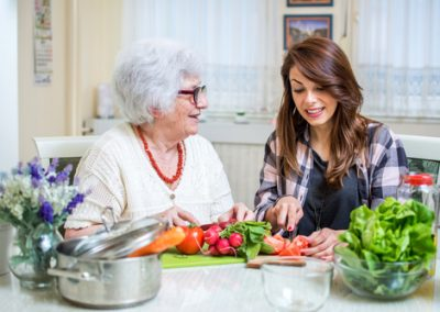 Grandmother and her granddaughter preparing healthy food togethe