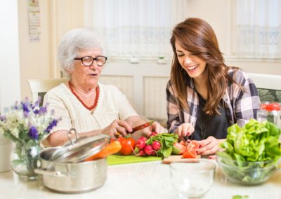 Grandmother and granddaughter preparing food at home.
